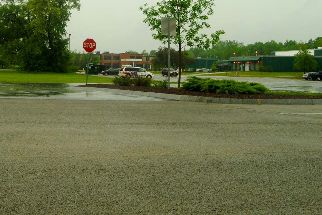 During heavy rains in Keene, impervious pavement in the distance causes stormwater runoff while new, permeable pavement (the part that looks dry) in the foreground allows stormwater infiltration