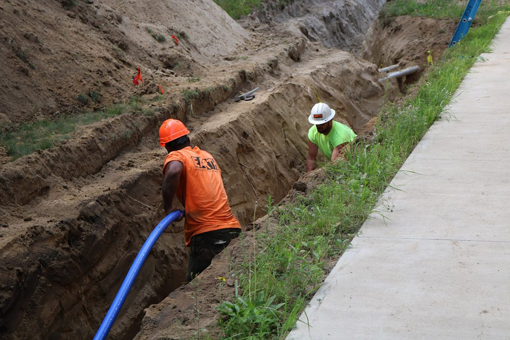 workers laying pipe in a trench